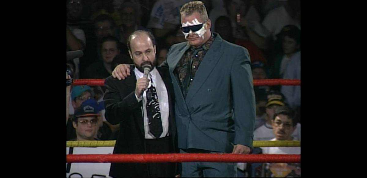 Tod Gordon stands in the ring with a bandaged Sandman wearing sunglasses