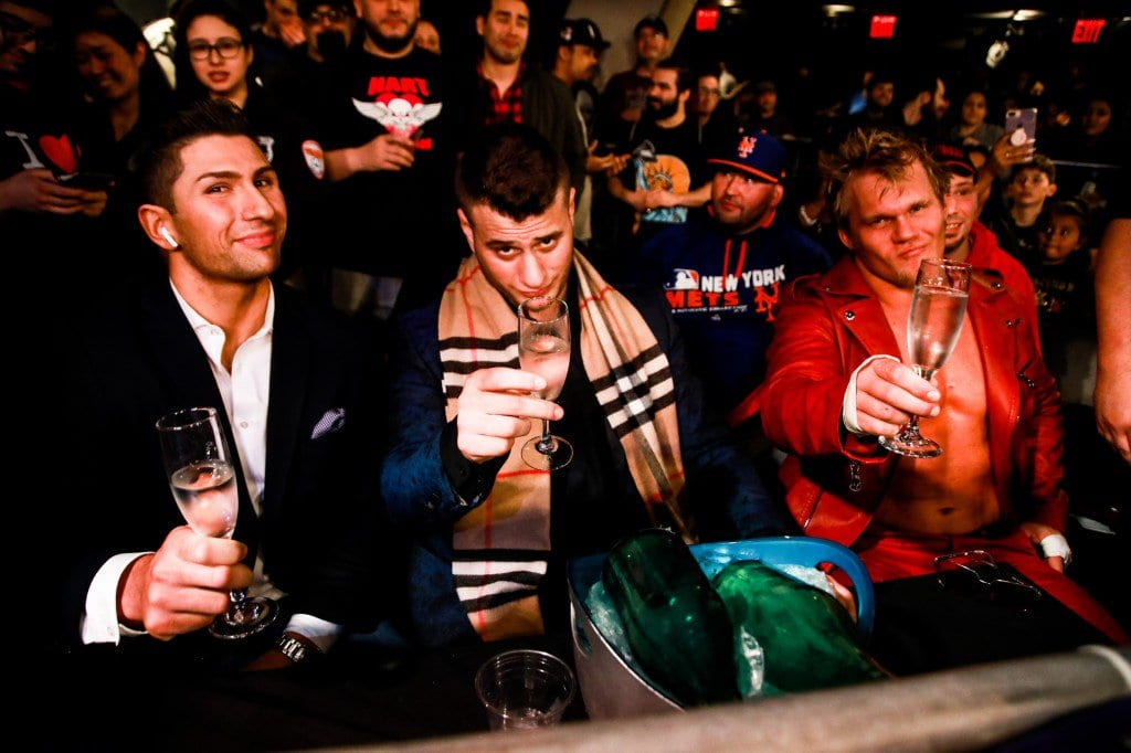 The Dynasty sit in the front row of a MLW show, sipping champagne and looking smug.