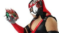 A picture of AAA Star Falmita staring at one of his own masks which he holds in this right hand