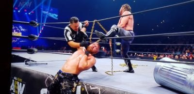 Kenny Omega wraps a chain around Jon Moxley's neck and hangs him from the side of the ring at AEW Full Gear 2019