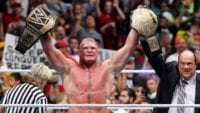 Brock Lesnar stands in the ring holding up the WWE Universal title and the Big Gold Belt, as Paul Heyman raises his arm