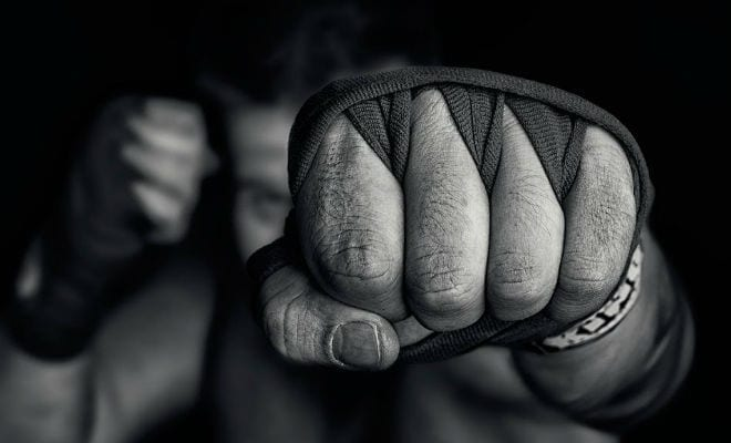 a black and white photo of a man's strapped hand punching