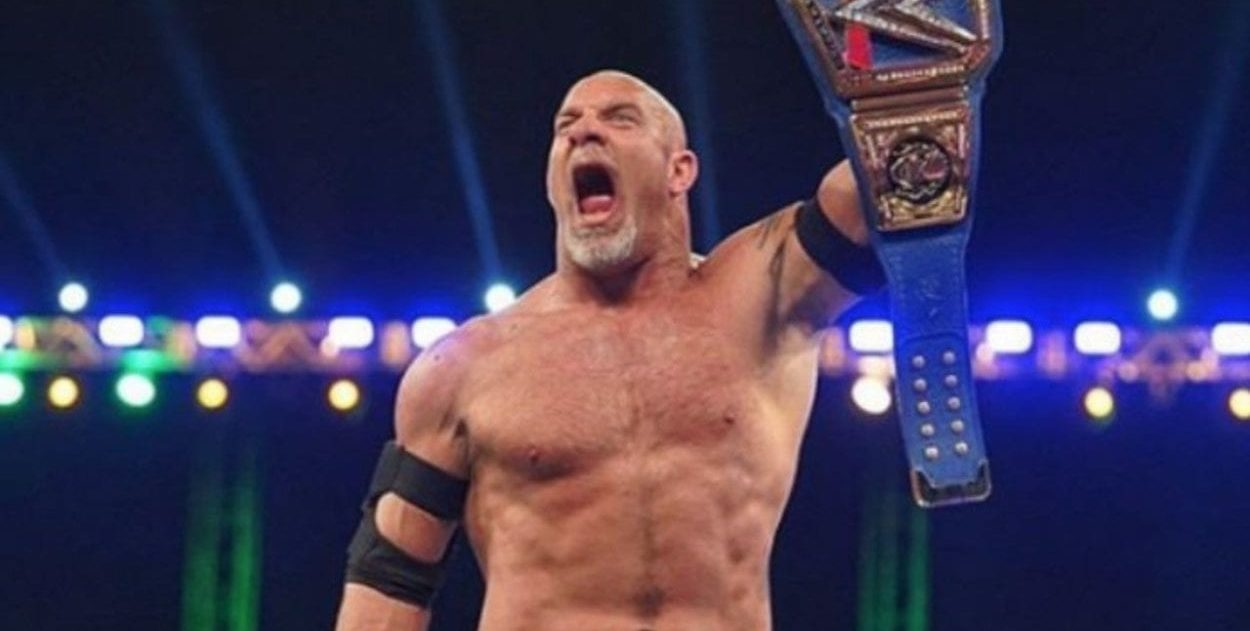 Goldberg holds up the WWE Universal title belt in victory