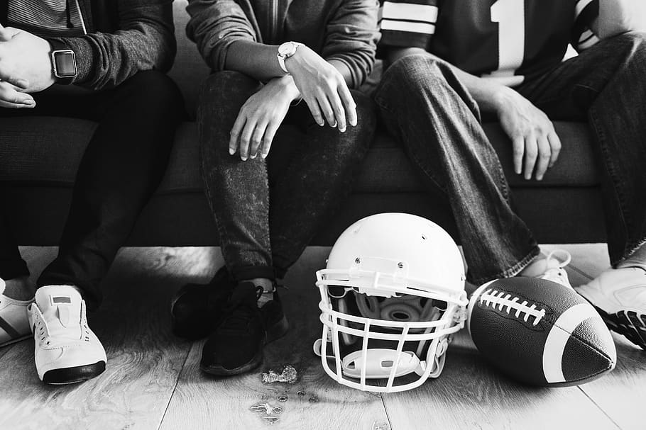3 men sit with a football and helmet