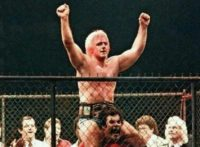 A bloody Ric Flair is held up by a group of wrestlers, arms aloft in victory