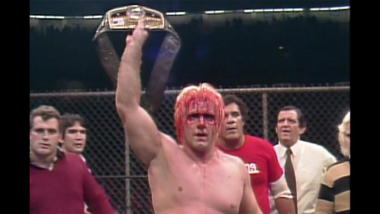 A bloodied Ric Flair holds up the NWA Heavyweight title as other wrestlers look on