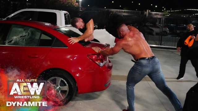 Brian Cage throws John Moxley against a car as Taz watches on