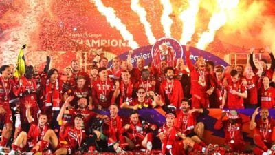 Liverpool players are grouped together. celebrating their title triumph with a large firewroks display in the background
