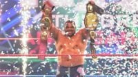 Keith Lee holds up both NXT singles titles underneath the ticker tape