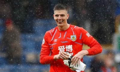 Nick Pope leaves the field wiht a smile on his face, as he takes of his gloves.