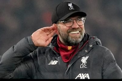 Jurgen Klopp holds a hand to his ear to his hear the crowd, as he leaves the pitch with a smile on his face