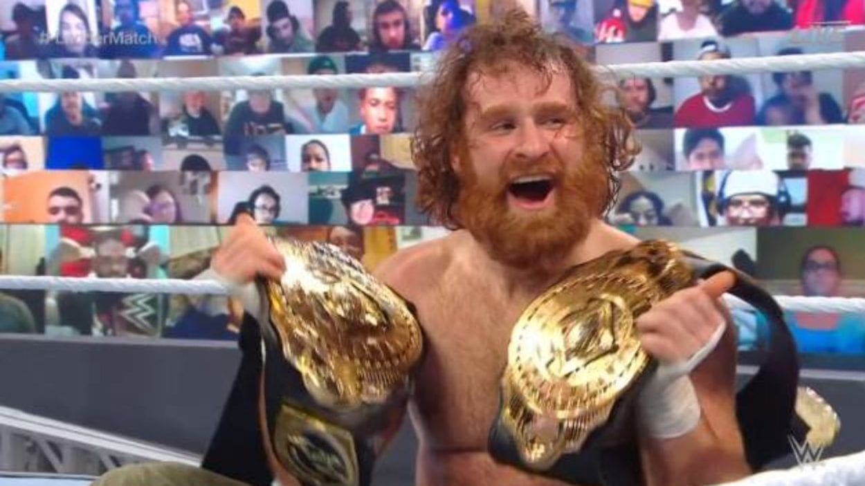 Sami Zayn poses with the Intercontinental belts