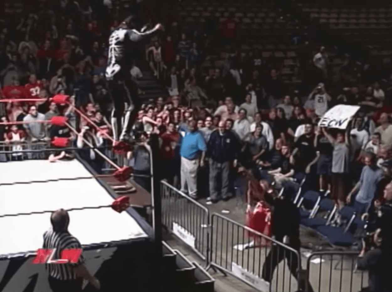 La Parka prepares to jump off the top and over the guard rail onto Sabu