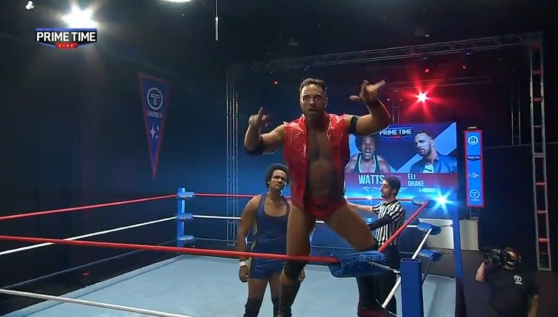Eli Drake poses on the turnbuckles as Watts stares him down