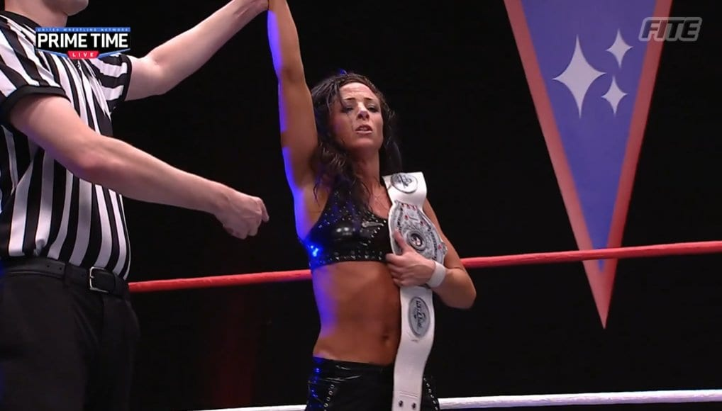 Serena Deeb has her hand raised as she holds the NWA Women's title