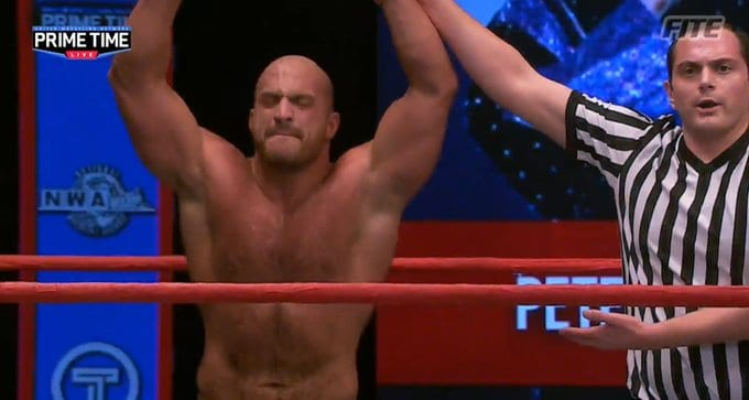 Chris Dickinson has his hand raised in victory on Prime Time Live