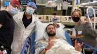 Finn Balor lies in his hospital bed surrounded by doctors