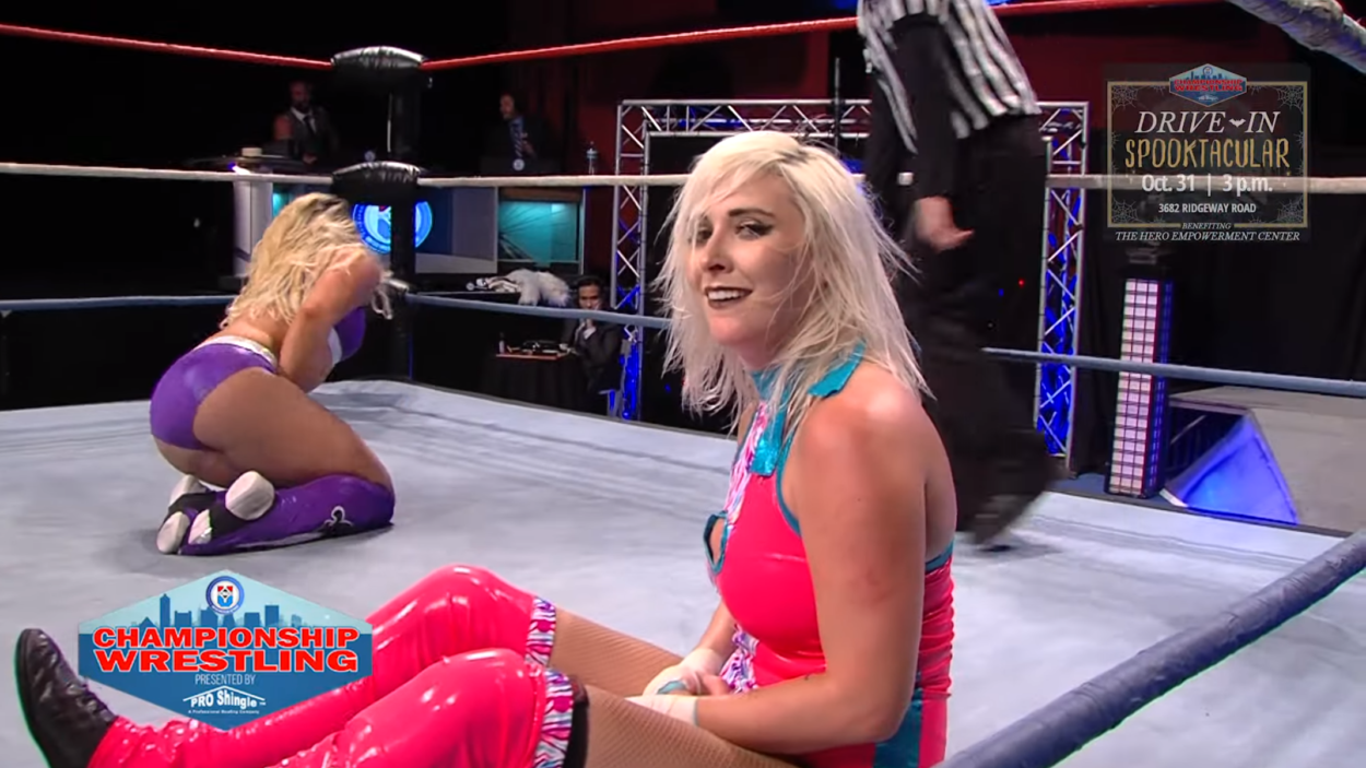 Heather Monroe smiles at the camera while Lacey Ryan writhes in pain