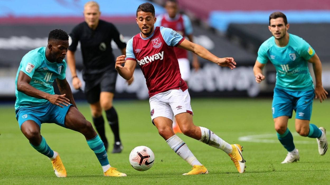 A West Ham player weaves between two opponents