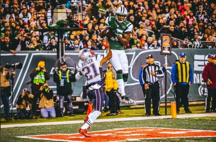 Brandon Marshall makes a leaping catch in the endzone while on the Jets. A Patriots defensive back tries to break up the catch. Marshall's first season with the Jets was one of the best receiver debuts of all time.