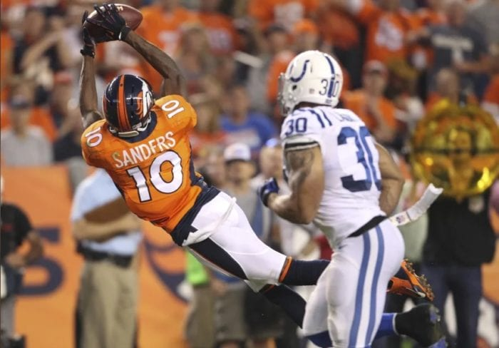 Emmanuel Sanders makes an athletic, diving catch with the Denver Broncos. A Colts defender is in the foreground. Sander's first season with the Broncos was one of the best receiver debuts of all time.