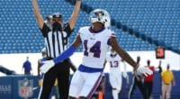 Buffalo Bills wide receiver Stefon Diggs debuts with the Bills in 2020. He is seen here scores a touchdown. Diggs' arms are outstretched, and behind him a referee signals touchdown.