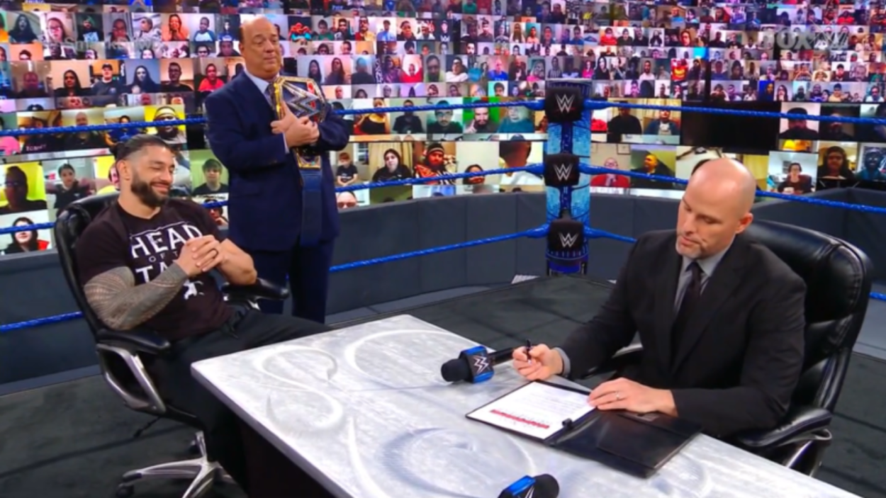 Adam Pearce signs the contract on SmackDown as Roman Reigns and Paul Heyman smugly look on