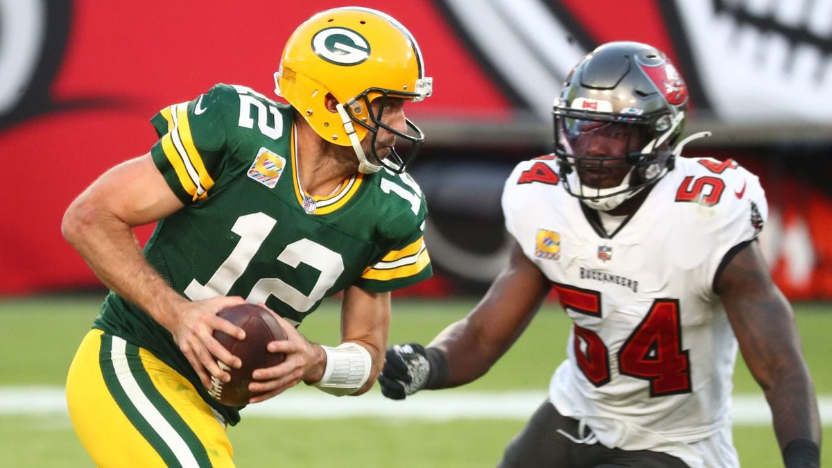 Aaron Rodgers holds the ball with two hands as he stares down a Tampa defender