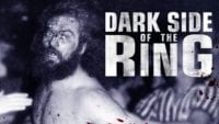 Screen shot of the Dark Side if the Ring Promo Image. Dark Side of the Ring is written in big white letters to the right side. Bruiser Brody is on the left side in black and white with blood on his face.