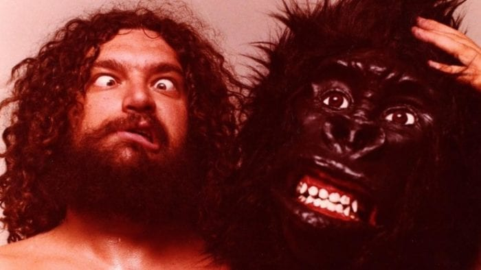 In this image, Bruiser Brody is making a dace holding a gorilla mask next to him.