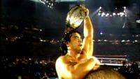 Ricky Steamboat holds up the Intercontinental title at WrestleMania 3 as George Steele carries him