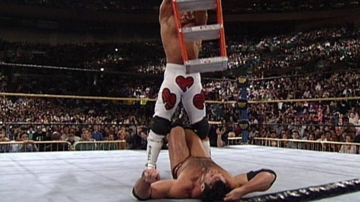 Shawn Michaels prepares to drop the ladder on a prone Razor Ramon during their match at WrestleMania 10