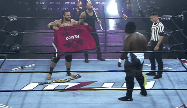Jacob Fatu holds up the CONTRA flag as Daivari watches - March 2021
