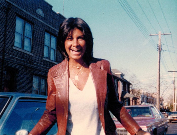 Nancy Argentino is standing in a white shirt and brown leather jacket. She is smiling.