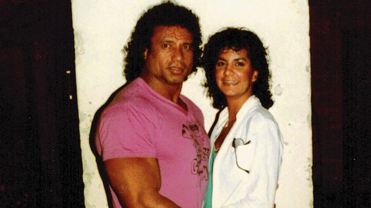 Jimmy Snuka is standing on the left side wearing a pink/purple shirt. Nancy is standing wearing a light blue shirt and white blazer to the right of the photo.