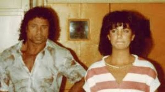 Picture of Jimmy and Nancy. Jimmy is wearing a light colored shirt. Nancy is wearing a white and pink striped shirt. Neither are smiling.