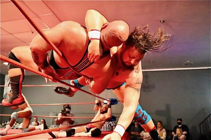 Justin Cole clotheslines Norman Meklakov over the top rope