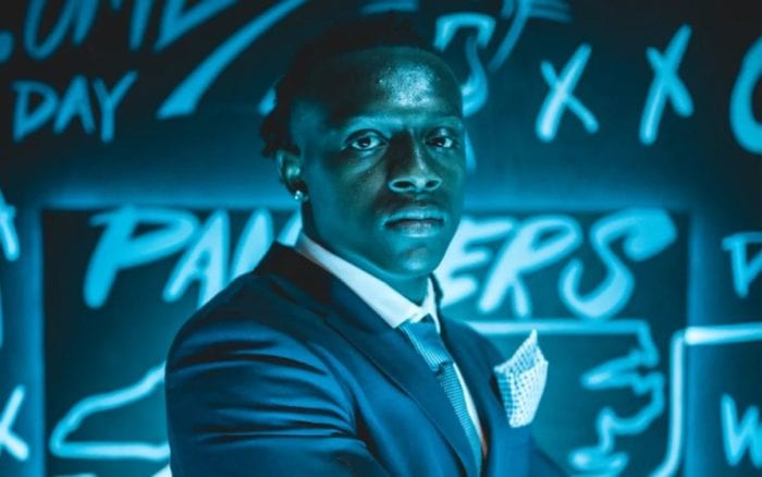 Jaycee Horn stands in front of a Panthers themed backdrop after being selected by the team in the 2021 NFL Draft.