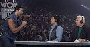 Scott Hall confronts Erich Bischoff and Bobby Heenan at the commentary desk