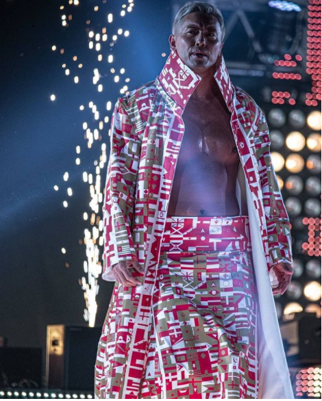 Okada walking down the ramp before a match wearing red and white.