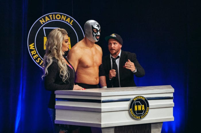 A mystery masked man interrupts Kyle Davis and May Valentine at the podium