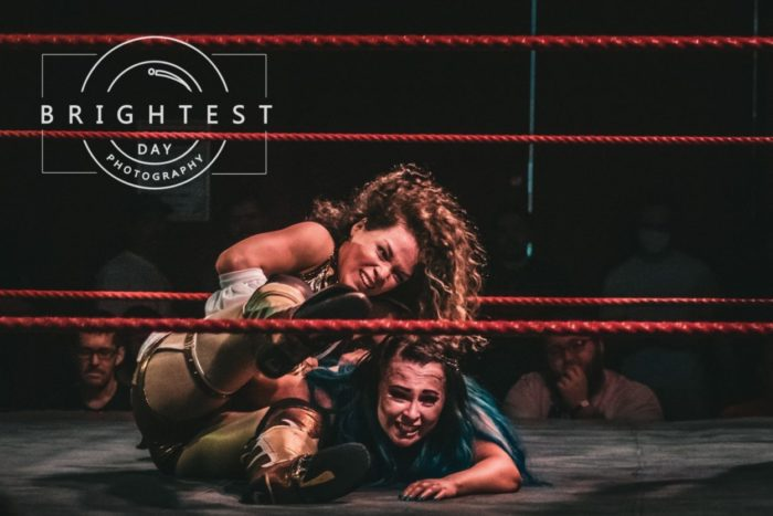 Clementine puts Ivy into a submission hold