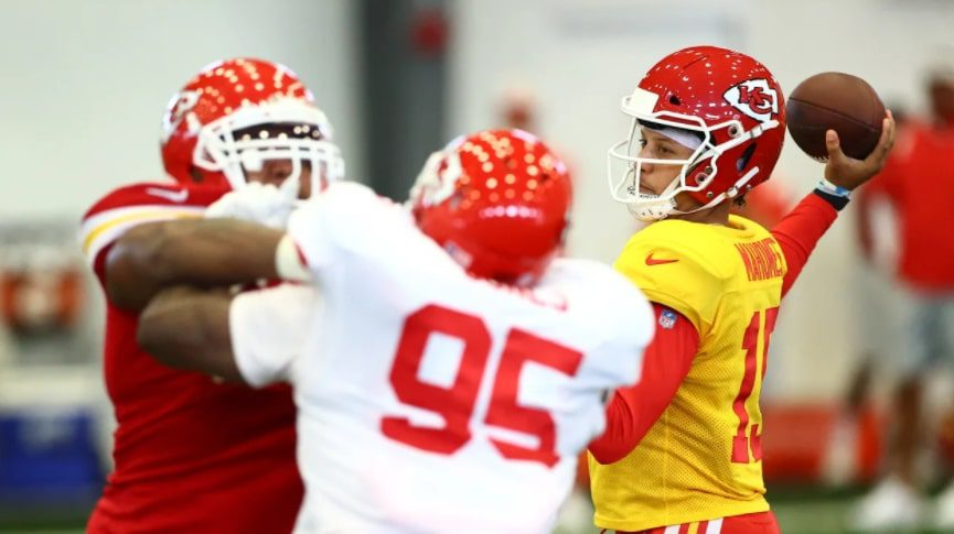 """Cover photo for """"Ranking Ever 2021 NFL Offense."""" Patrick Mahomes at practice during training camp. An offensive lineman is blocking a defender in the foreground."""