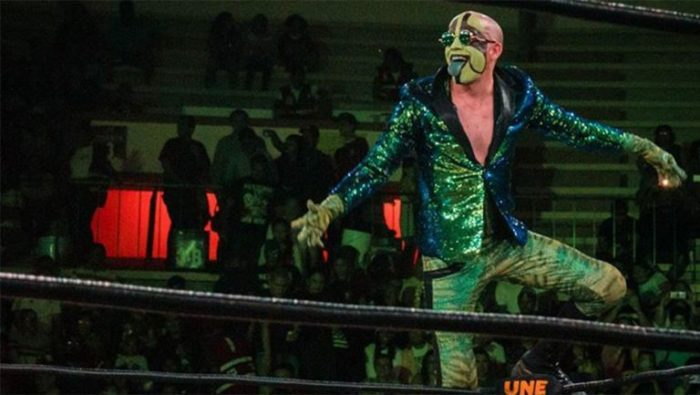 Mr. Iguana enters the ring wearing green sunglasses and a sparkly green jacket.