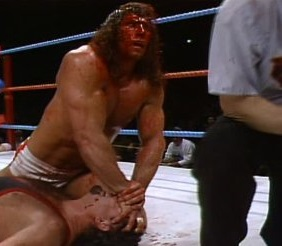 A bloody Kerry Von Erich locks Jerry Lawler in the Claw