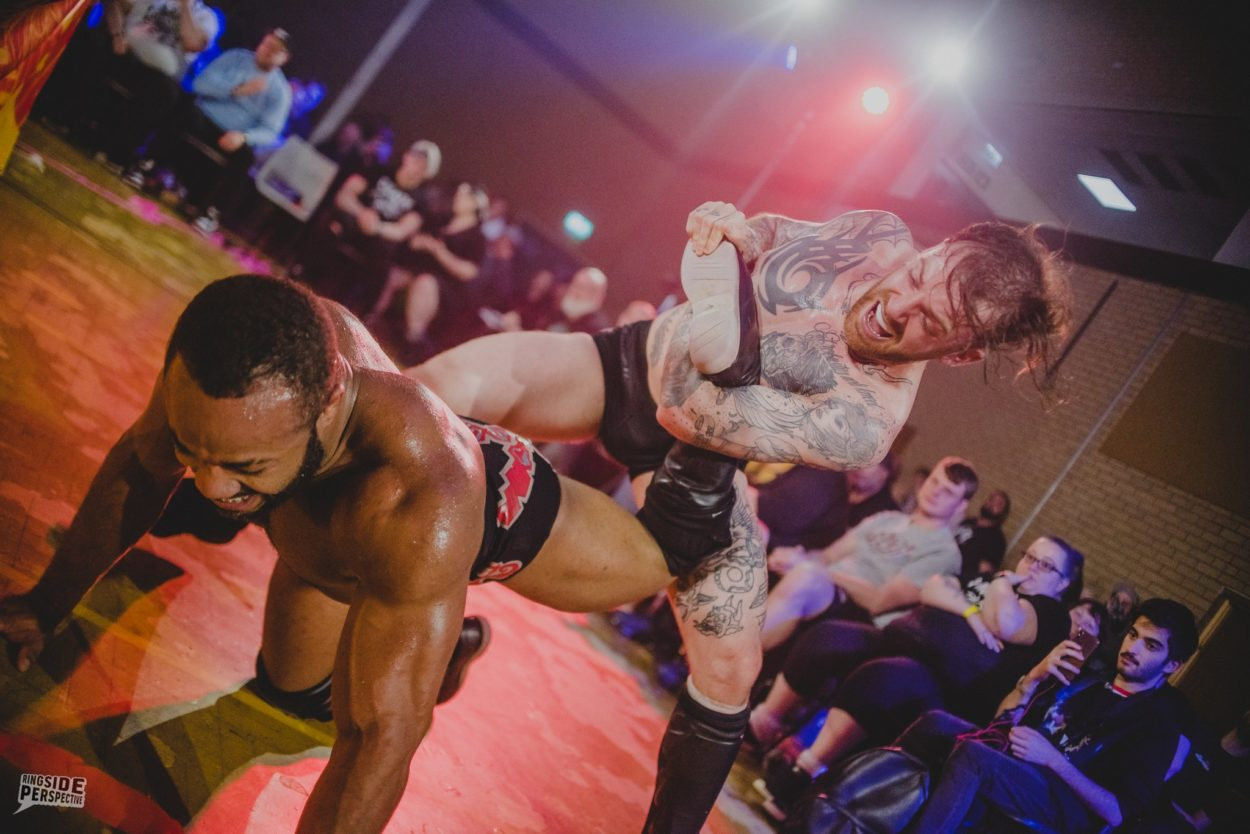 Chris Ridgeway tries to snap Jonathan Gresham's ankle at ringside at Wrestle Carnival 'PURE'