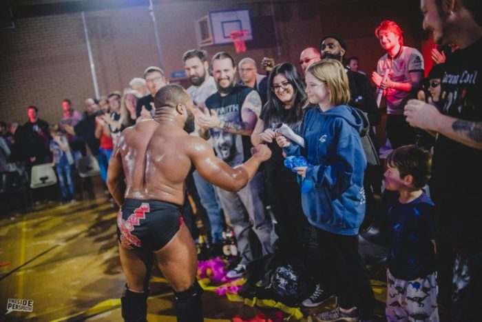 Jonathan Gresham bumps fists with the fans at Wrestle Carnival